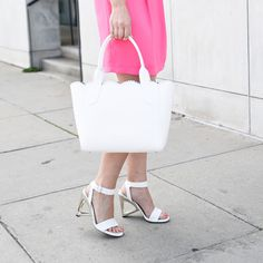White strappy sandals with a metallic cutout heel.