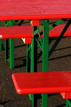 red picnic tables and benches with green, metal legs