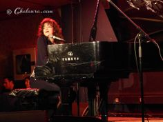 Carmen París tocando el piano y mirando hacía el público