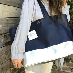 """SALE‼️NWT Kate Spade Conrad Lita Galaxy Luxe Tote Omgosh where to even begin with this one!! From the Madison Avenue Collection. 100%pebble leather. NWT includes care card and dust bag. Dark navy blue and metallic silver. Hard to find. In pristine condition except some light scratches around the silver part and minor wear on one corner bottom. 21"""" wide, 14""""tall, handles are an additional 11"""" long. Metal KS silver logo. Perfect for yoga class, meditation retreat, a weekend getaway or a trip…"""