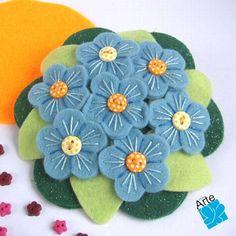 Fivela com bouquet de flores de feltro, bordadas e com aplicação de botões.  Dimensões: 11 cm de diâmetro.  Acabamento perfeito, com fivela longa. R$ 30,00