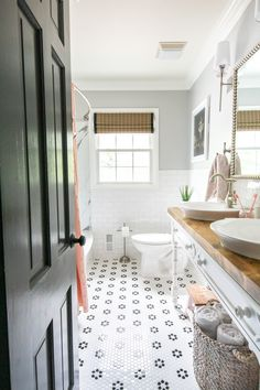 Whimsical, classic kids bathroom makeover | open vanity table with step stools and vessel sinks, faux marbled shower, subway tile and more! #bathroomreno #homeimprovement