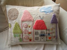 embroidered houses on pillow by Isabel Freire