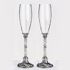 "Beaded Toasting Flutes - WeddingDepot.com - 047-G920-NI This pair of elegant toasting glasses stands 10.5"" tall.  A series of silver and clear beads decorate the middle portion of the stems.  Customize the set to your own color by adding a set of beads in the color of your choice.  To personalize this glass set, you can easily remove the beads and replace them with your own special beads.  Simply unscrew the base from the threaded rod."
