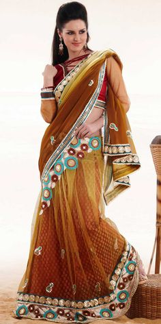 Embroidered sarees are the best choice for a girl to enhance her feminine look.   This brown and yellow faux georgette, net and brocade lehenga style saree is nicely designed with embroidered patch work is done with resham, zari, stone and lace work.   Beautiful embroidery work on saree make attractive to impress all.   This saree gives you a modern and different look in fabulous style.   Contrasting maroon blouse is available.