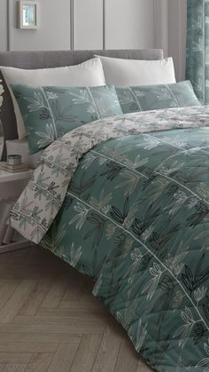 The big, bold leaf design on the Imogen teal cotton rich duvet set will add a splash of modern pattern and style to any bedroom. The duvet set features a mix of natural, charcoal grey and white leaves on a white stem, printed on a rich teal background. The duvet cover is fully reversible, offering a bright white background printed with teal and charcoal toned leaves. Complete the look with the matching bedspread and curtains.