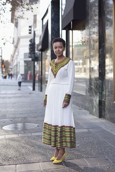 This image shows a woman wearing the African habesha kemis. A habesh kemis is an ankle length dress that is made of chiffon that usually is white, grey, or beige shades.Many women wear a shawl called a netela around the formal dress. The habesha kemis is worn by Ethiopian and Eritrean women at formal events.