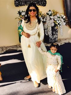Mom & her baby girl in same ethic Indian clothes during a big fat Indian wedding