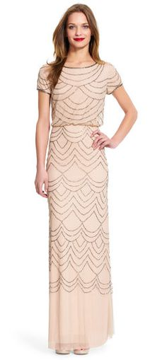 Classic charm and effortless sparkle team up in this gorgeous evening gown featuring a beaded blouson bodice that creates a flattering look. The beaded design continues down a long flowing skirt. Short sleeves and a scoopneck complete this pretty dress.