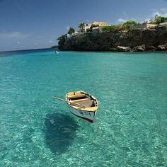 The crystal clear water surrounding the island Curacao. The boat looks like it's above the water.