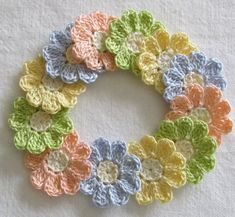 12 small cotton thread crochet flower appliques, embellishments in pretty pastels.  The centers are cream. The petals are maize yellow, wasabi green, bridal blue, peach.  ** Remember that monitors vary when showing colors. These are pastels.  Sew or glue these pretty little flowers to all your crafts - add to scrapbook pages, greeting cards, hair clips, clothes, crafts, picture frames - so many uses.  Each flower has 9 rounded petals They are approximately 1 1/4 (1.25) inches.  Crocheted in…