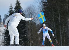 Macus Hellner of Sweden is handed a flag by a team member as he completes the final lap of the Cross Country Men's 4x10km Relay (c) Getty Images