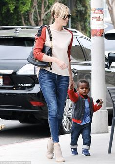 Charlize Theron out for lunch with son Jackson at BLD in Hollywood, California, September 2013. Mommy's little helper: Jackson, 17 months, looked super cute in cuffed jeans, blue sneakers, matching T-shirt and grey and red varsity jacke...