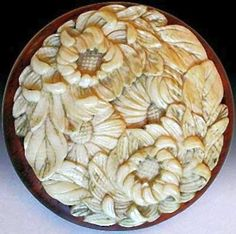 A beautiful 19th century carved ivory button of flowers and leaves. Mounted in a metal collet.