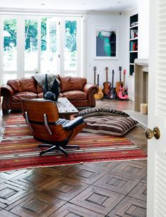 Living room with Eames lounge chair and guitars in corner. The floor!