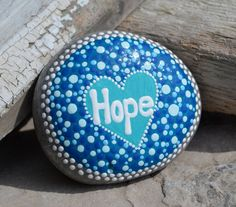 Lovely smooth beach stone painted with dots, blues & whites, and the word HOPE. Great gift for someone struggling in life. This gem measures approx 3x2.5 is signed and dated and has had a coat of varnish to seal and protect, Enjoy! Not suitable for children