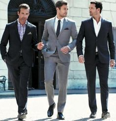 Men on the right and left are in business casual attire. No tie, top button of shirt is unbuttoned. Man in middle is wearing business professional attire.