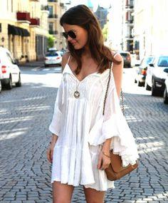 Robe blanche courte pour un look bohème chic joliment accessoirisé par un sac à main cuir