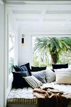House tour: a cost-conscious and unfussy holiday home in Sydney's Palm Beach: Outdoor fabrics were selected for some of the upholstered interior pieces, the white-painted floorboards are easily cleaned — and while there are several seating and dining areas, the three-bedroom house feels not only proportionate but ideal for either a couple or a large group.