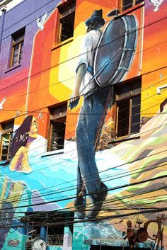 Street art including a Chinchinero in Valparaiso, Chile. A Chinchinero is an urban street performer in Chile, usually a man or young boy, who plays a bass drum-type percussion instrument with long drumsticks.