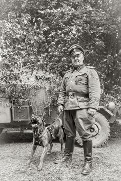 A Officer with his viscous dog next to a camoflaged SdKfz 222 armored car