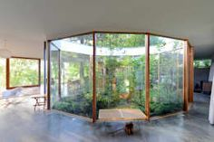 Encased in glass on all sides, this oval courtyard is the showstopper in this house. Paired with the glass walls on the other side, it ensures that the interiors stay warm, well-lit and inviting throughout the day. A beautiful garden is being grown inside the courtyard and this adds to the décor of the home. Design by NO Architecture