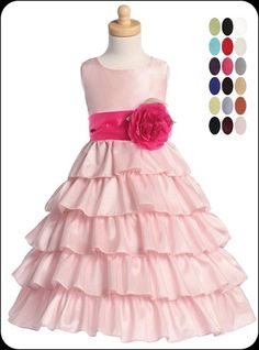 Tiers of shimmering taffeta tumble down an elegant pink flower girls dress fashioned with a sleeveless bodice, a beautiful bloom adorns the empire waist that cinches back with a sash in your desired color.