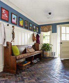 A slate floor by Artistic Tile is laid out in a herringbone fashion and accented by a one-of-a-kind pew found on eBay and Benjamin Moore Phillipsburg Blue walls to create a dramatic back-entrance in this Neocolonial Revival. | Photo: Laura Moss | thisoldhouse.com