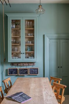 Sustainable Kitchens - Cotswold Chapel Kitchen. Glazed oak cabinet with LED lights painted in Farrow & Ball Chappell Green maximise the space by making the most of the high ceilings. Pine table with chapel chair hint at the origins of the house as an old chapel.