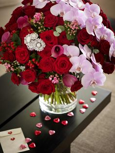This stunning Valentine's Day floral arrangement includes beautiful red roses and pretty pink orchids