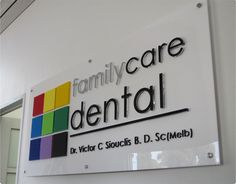 Flat Cut Acrylic Letters: Flat cut CNC letters with flame polished edges, having coloured vinyl applied to front and fixed to white acrylic panel.  Non-lit and fixed to interior wal with stand-off hardware.