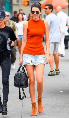 Street style look Kendall Jenner usando uma blusinha laranja, saia jeans básica, ótima para o verão, e botas de camurça bege