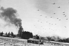 Low flying C-47 transport planes roar overhead as they carry supplies to the besieged American Forces battling the Germans at Bastogne, during the enemy breakthrough on Jan. 6,1945 in Belgium. In the distance, smoke rises from wrecked German equipment, while in the foreground, American tanks move up to support the infantry in the fighting. (AP Photo).