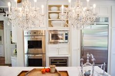 Double crystal chandeliers over kitchen island.  Shawna's Glamorous Custom Kitchen — Kitchen Tour | The Kitchn