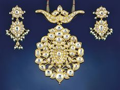 An Indian, white sapphire pendant necklace and earpendants  The large pendant of openwork floral design with pear shaped cluster centre to a yoke surmount, set throughout with foiled flat-cut colourless sapphires, to a cord fastener; the foiled flat-cut colourless sapphire earpendants with shaped cluster drops to flowerhead surmounts, with imitation pearl and glass bead fringe decoration, the reverse with polychrome enamel floral decoration, hook fittings