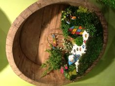 Fairy garden in the siding of the bottom of a whiskey barrel. Adorable.