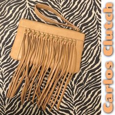 """Fringe Clutch by Carlos NWOT Carlos by Carlos Santana fringe clutch, brand new without tags!  Perfect for summer!  Measures 10"""" by 6"""" with a 7"""" strap. Cell phone pocket, zipper inside pocket, small pocket on back with a magnetic closure.  Get it here and SAVE!  No trades or Paypal! Carlos Santana Bags Clutches & Wristlets"""