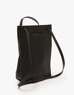 From Chiyome, a large black leather tote pack with minimalist styling. Features single strap that doubles as top handle or shoulder straps, tab handle, interior back pocket and back panel. • Large black leather tote pack • Adjustable strap to functi