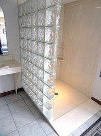 Roll in cultured marble shower pan with a wavy pattern glass block wall.