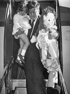 John F Kennedy exits the plane carrying his daughter Caroline and her Raggedy Anne doll - October 1960.