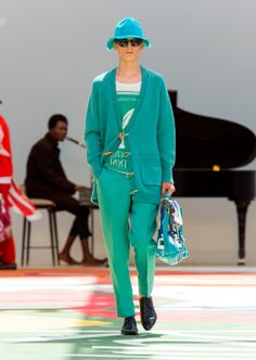 A wash of aqua green on a cashmere duffle cardigan, linen tapered trousers and the campaign hat