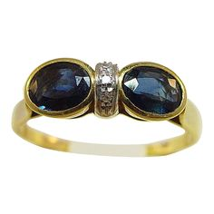 This lovely 18 karat yellow gold* ring features 2 oval shaped sapphires with a single, vertical row of 3 bead set diamonds in between them. The ring