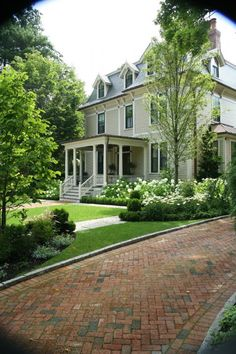 Exterior- herringbone design brick driveway. Terracotta and grey bricks. Neutral paint on house. Lovely landscaping.