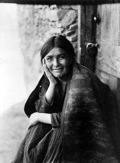 Portrait of a Navajo woman sitting in her doorway, smiling. Photographed by Edward Curtis, 1904.