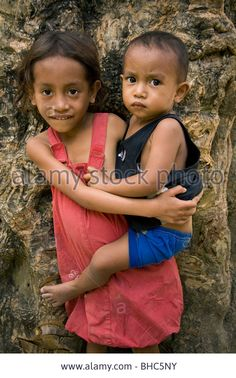 Young Timorese girl caring for her baby brother in mountain region above Dili East Timor Stock Photo