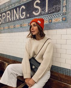 love this red beanie hat with a cream color outfit, cream color knit sweater and pants and an orange red beanie hat, pop of red outfit,