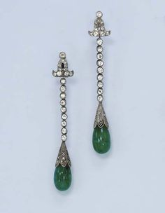 A PAIR OF DIAMOND AND EMERALD EAR PENDANTS. Each emerald drop, with a rose-cut diamond cap, suspended by a diamond collet line to the old European-cut diamond surmount of foliate design, mounted in platinum