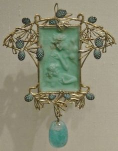 RENÉ LALIQUE. Art Nouveau pendant, rectangular green jadeite (?) panel with ladies/elves in relief, gold or gilt silver surrounding branches with grey blue enamelled pine cones, dangling bead, possibly turquoise. Ca. 1900