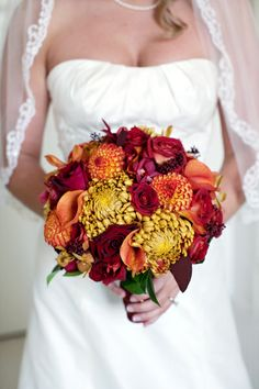 Bronze colored football mums, were used with orange dahlias, orange callas, orange orchids, red and brown roses, and red seeded euc.