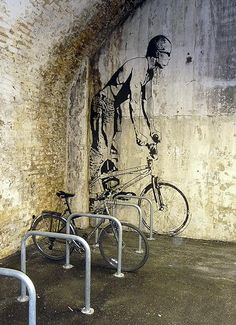 Beautiful Banksy piece on a wall beside some bike racks.  Is this London?